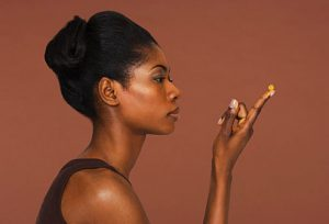 getty_rf_photo_of_woman_contemplating_a_vitamin
